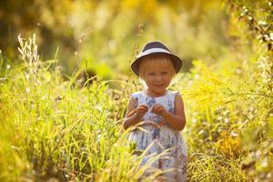 klein blond meisje in een jurk en hoed foto