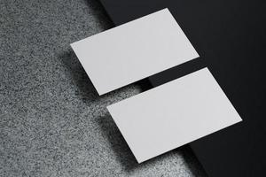 witte horizontale papieren mockupsjabloon voor visitekaartjes met lege ruimtedekking voor het invoegen van bedrijfslogo of persoonlijke identiteit op zwarte kartonnen vloerachtergrond. modern begrip. 3d illustratie render foto