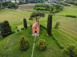 drone-weergave van pas getrouwd stel in de rode kerk van pomelasca foto