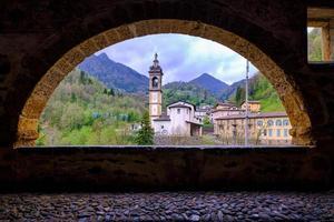 schilderachtig uitzicht op de oude kerk vanuit een prachtige oude arcadenstraat foto