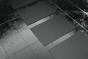 zwarte horizontale papieren mockup-sjabloon voor visitekaartjes met lege ruimtedekking voor bedrijfslogo of persoonlijke identiteitsrij die op betonnen vloerachtergrond schikt. selectieve aandacht. 3d illustratie render foto