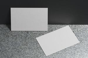 witte sjabloon voor visitekaartjespapier met lege ruimtedekking voor het invoegen van bedrijfslogo of persoonlijke identiteit op marmeren vloerachtergrond. modern begrip. 3d illustratie render foto