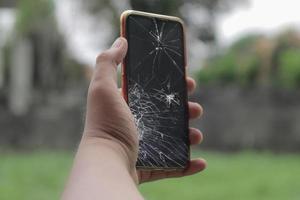 hand met gebroken lcd-glas van mobiele telefoon gebarsten en gebroken foto