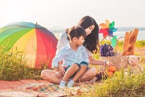 mooie aziatische moeder en zoon die picknicken en in het paaszomerfeest op de weide in de buurt van het meer en de bergen. vakantie en vakantie. mensen levensstijl en gelukkig gezinsleven concept. Thaise persoon foto
