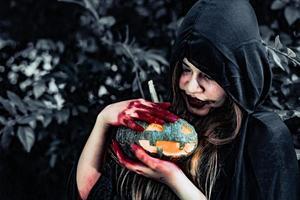 demonheks zorgt voor pompoen in het mysteriebos. spook en horror concept. Halloween dag thema. rood bloed aan heksenhanden foto