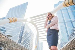 schoonheidszakenvrouw die mobiele telefoon gebruikt om te communiceren met klanten in de stad. bedrijfs- en technologieconcept. metropool thema foto