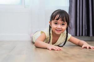 portret van een schattig klein meisje dat met blote voeten op de vloer ligt en thuis naar de camera kijkt. mensen levensstijl concept foto