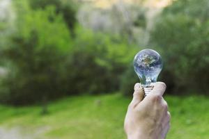 mannelijke hand met aarde glazen bol foto