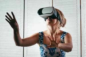 vrouw die een vr-bril draagt en haar hand in de lucht wijst foto