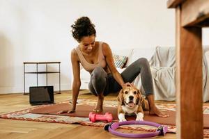 zwarte jonge vrouw lacht en aait haar hond tijdens yoga practice foto