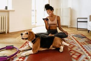 zwarte jonge vrouw die mobiele telefoon gebruikt terwijl ze met haar hond op de mat zit foto
