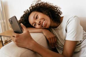 zwarte jonge vrouw die mobiele telefoon gebruikt terwijl ze op de bank rust foto