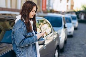 meisje op een stedelijke achtergrond, kijkend naar iets aan de telefoon, leunend op de auto foto