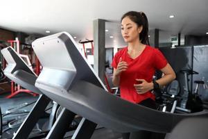 Aziatische vrouwen lopen sportschoenen in de sportschool terwijl een jonge blanke vrouw jogt op de loopband foto