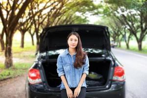 gestresste vrouwen na autopech met rode driehoek van een auto op de weg foto