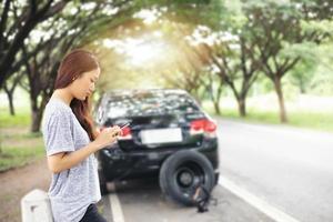 Aziatische vrouw die mobiele telefoon gebruikt terwijl ze kijkt en gestresste man zit na een autopech op straat foto