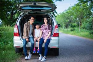 gelukkig klein meisje met aziatische familie die in de auto zit om te genieten van een roadtrip en zomervakantie in een camper foto