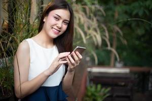 Aziatische zakenlieden en vrouwen gebruiken mobiele telefoons en raken smartphones aan voor communicatie en het controleren van zakenmensen op kantoorachtergrond foto