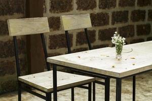glas met bloemen op vintage houten tafel foto