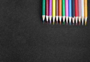 tekenbannerconcept, kleurrijke potloden in de rechterbovenhoek op zwart canvas met textuur. foto