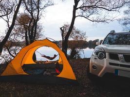 vrouw die op de hangmat aan de oever van het meer ligt. herfst camping concept foto