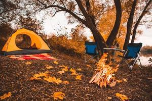 camping herfstplaats met vreugdevuur en draagbare stoelen foto
