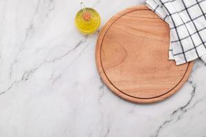 lege houten pizzaschotel met servet opgezet op marmeren stenen keukentafel. pizza bord en tafelkleed op witte marmeren achtergrond. foto