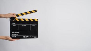 twee handen houden zwart met gele klepel bord op een witte achtergrond. foto