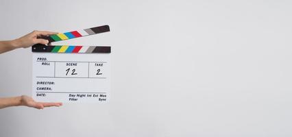 een hand houdt klepelbord of filmleisteengebruik in videoproductie en film-, film-, bioscoopindustrie op zwarte achtergrond. het heeft in nummer geschreven. foto