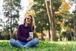 mooie vrouw die koffie drinkt in het park foto