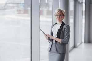 Glimlachende zelfverzekerde zakenvrouw die naar de camera op kantoor kijkt foto