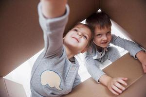 twee kleine jongens en meisjes die een kartonnen doos openen en er middenin klimmen. kinderen hebben plezier foto