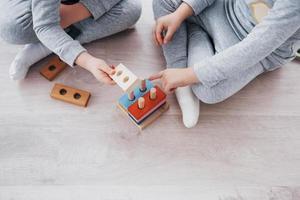 kinderen spelen met een speelgoedontwerper op de vloer van de kinderkamer. twee kinderen spelen met kleurrijke blokken. educatieve spelletjes voor de kleuterschool foto