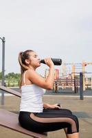 gelukkige vrouw die op het sportveld traint op een zonnige zomerdag, drinkt water uit de fles foto