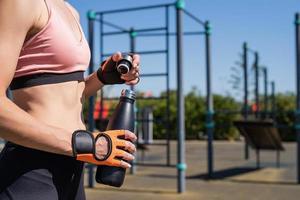 close-up van de handen van de vrouw in sporthandschoenen die een waterfles op het sportveld houden foto