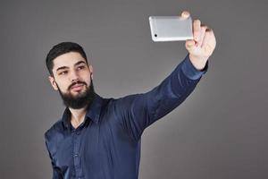 jonge, bebaarde hipster zakenman praten selfie foto met slimme telefoon glimlachen en kijken naar telefoon tegen grijze studio achtergrond