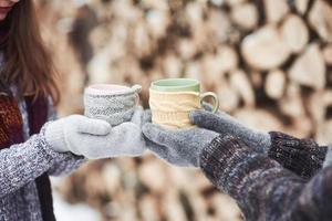 paar handen in wanten nemen een mokken met hete thee in het winterpark foto
