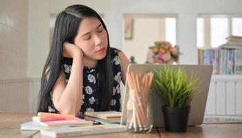 een universiteitsstudentenvrouw zat en sloot haar ogen terwijl ze thuis online studeerde. foto
