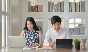 vrouwelijke en mannelijke studenten gebruiken laptops om thuis de zomer online te studeren. foto