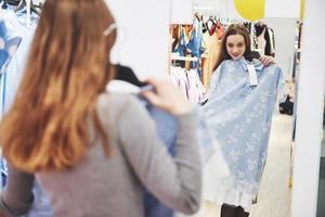 verkoop, mode, consumentisme en mensenconcept - gelukkige jonge vrouw met boodschappentassen die kleding kiest in winkelcentrum of kledingwinkel foto