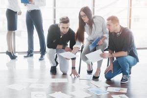 jonge creatieve mensen in moderne kantoren. groep jonge zakenmensen werken samen met laptop. freelancers zittend op de vloer. samenwerking corporate prestatie. teamwork concept foto