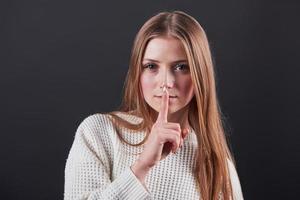 close-up portret van mooie jonge vrouw in witte trui en jeans, geïsoleerd op zwarte achtergrond foto