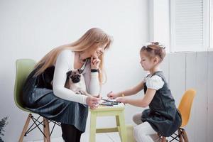 moeder en kind dochter trekt zich bezig met creativiteit in de kleuterschool. kleine mopshond met hen foto