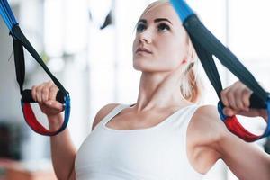 vrouwen doen push-ups training armen met trx fitness bandjes in de sportschool concept workout gezonde levensstijl sport foto