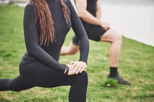 fitness paar die zich uitstrekt buiten in het park in de buurt van het water. jonge, bebaarde man en vrouw die 's ochtends samen trainen foto