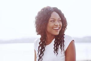 portret van lachende jonge zwarte vrouw met zonlicht flare foto