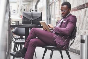 een mooie Afro-Amerikaanse zakenman leest een menu in een café foto