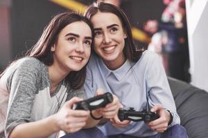 tweelingzusjes spelen op de console. meisjes houden joysticks in hun handen en hebben plezier foto