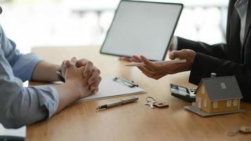 verzekeringsagenten met tablet introduceren vastgoedverzekeringsprogramma's voor klanten. foto