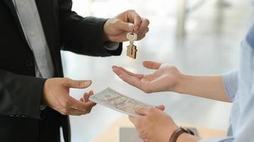 klanten en verhuurders wisselen geld en sleutels uit nadat ze hebben ingestemd met de aankoop van een huis. foto